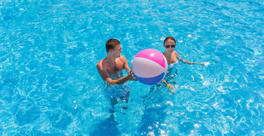 Young couple in a swimming pool with a beach ball